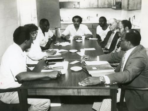 image of eight individuals sitting around a table hosting a meet on bus boycotts