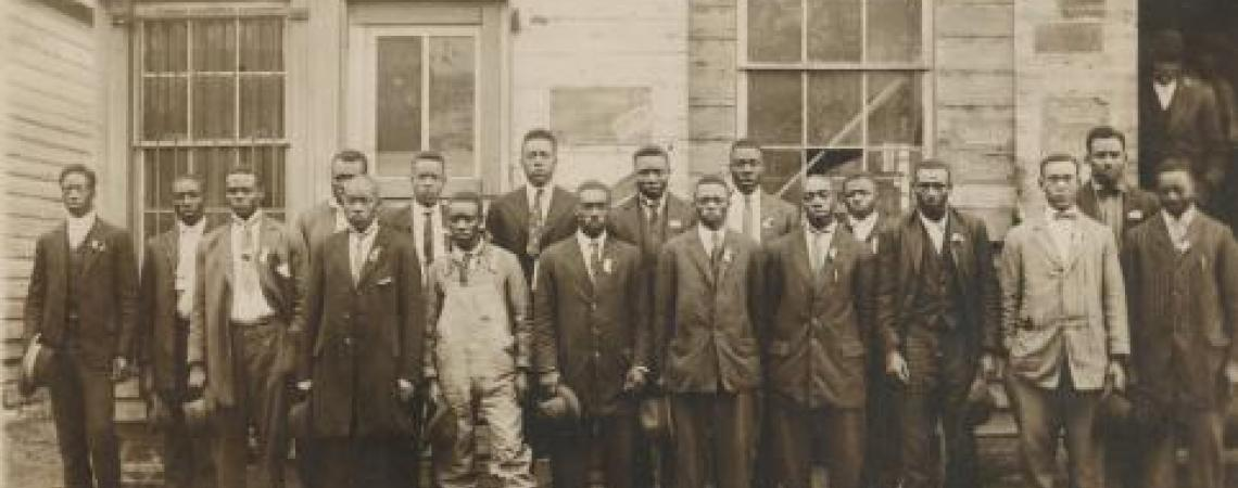 Group of African American men pose in front of draft office, 1900s.