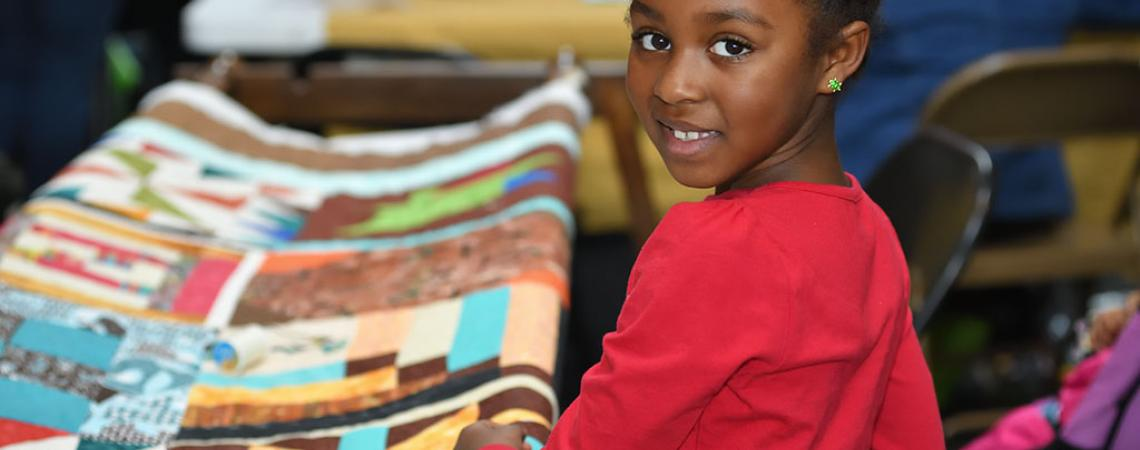 image of child viewing a quilt at the celebration event