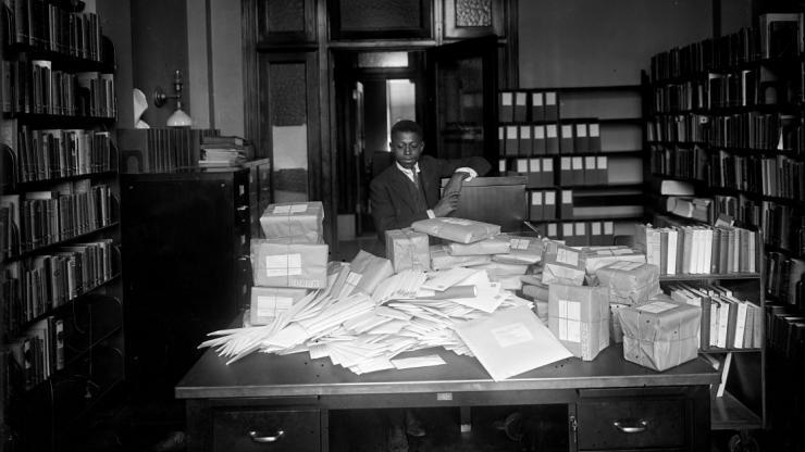 young African American boy standing behind a desk covered in letters and packages