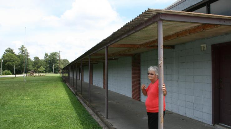 Brenda Moore, member of the Waccamaw-Siouan Tribe stands outside her childhood school, Waccamaw Indian School