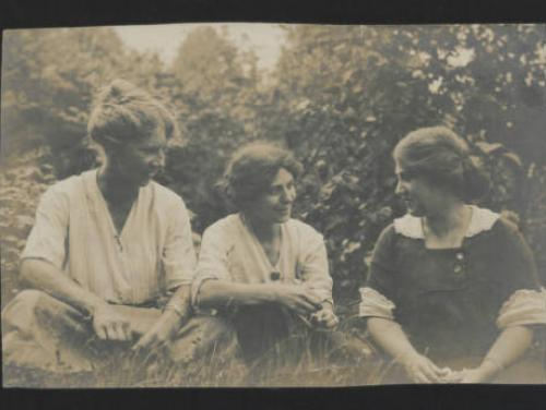 sepia-toned photograph of 3 women sitting on the grass and smiling at each other