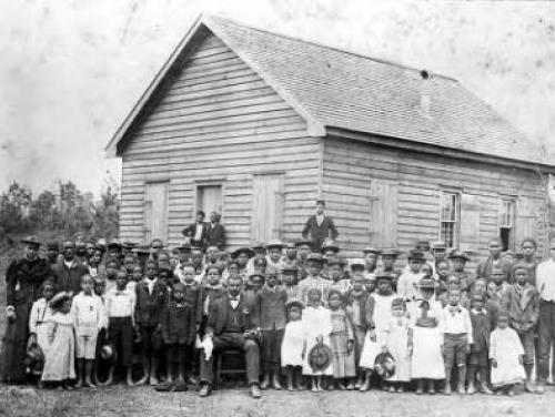 old black and white photo of children gathered in front of a school house