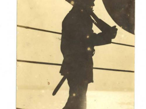 sepia-toned photograph of a silhouetted man holding a rifle