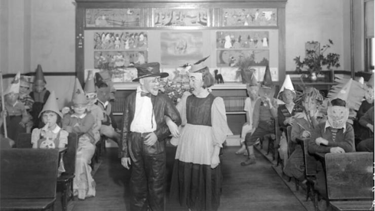 Black and white photo of children wearing Halloween maskes and costumes in a classroom, some children standing, others sitting at their desks