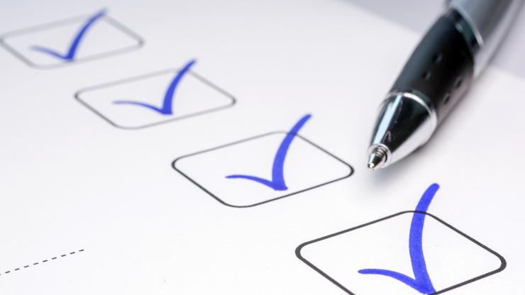 Pen lying on paper that has four check boxes checked off