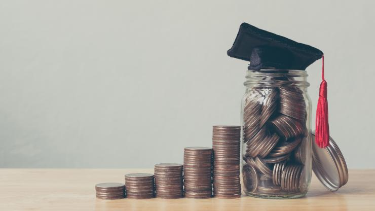 Stacks of coins with increasing amounts, like a graph, with a jar at the end and a graduation cap on top