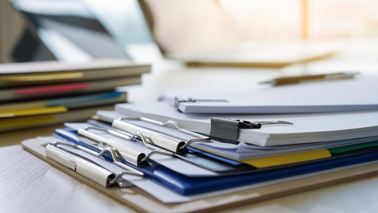 Two stacks of documents clipped with binder clips and three clipboards under them