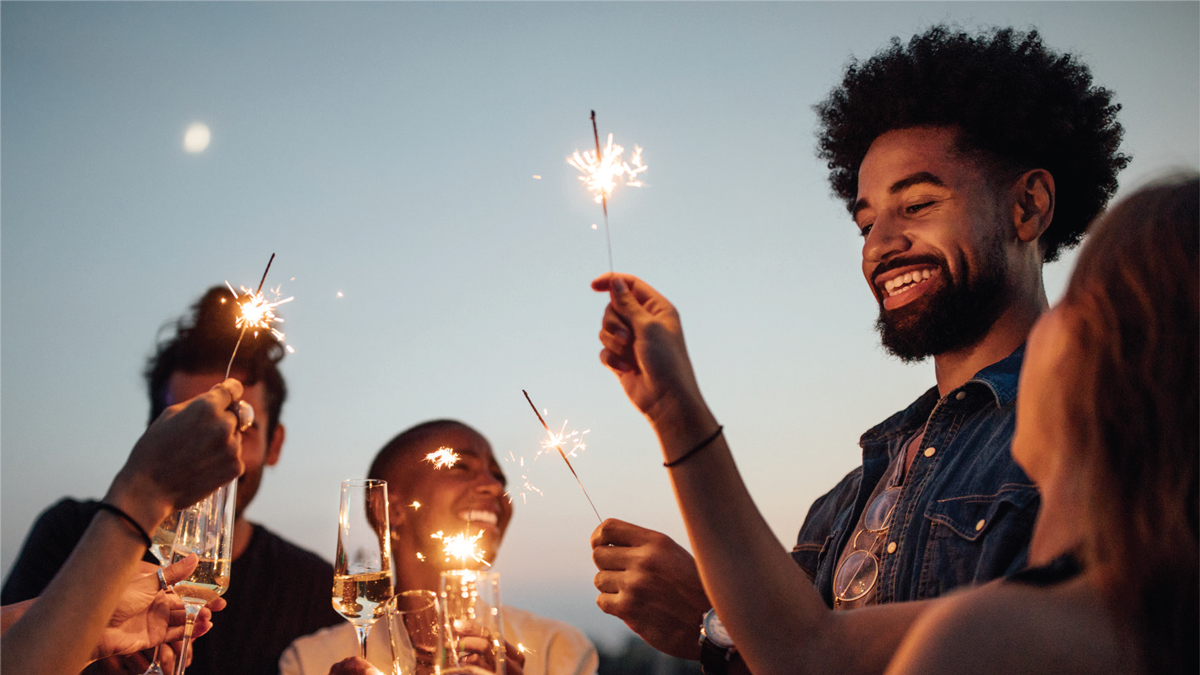 smiling people holding sparklers and glasses of wine