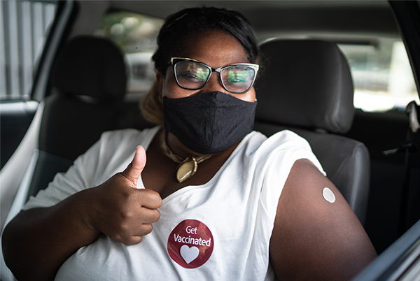 Woman with sleeve rolled up giving thumbs up and wearing Get Vaccinated sticker