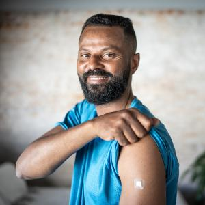 A smiling man shows off his arm after being vaccinated.