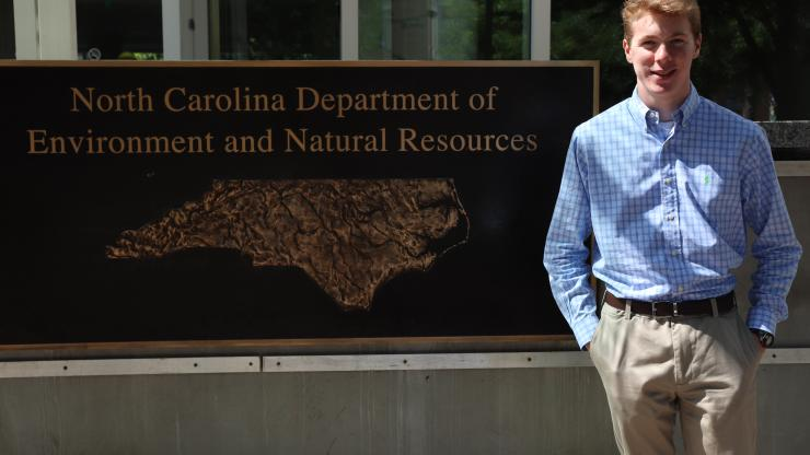 intern standing in front of sign