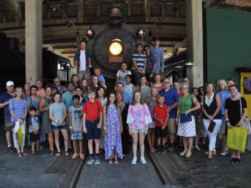 group of students in front of train