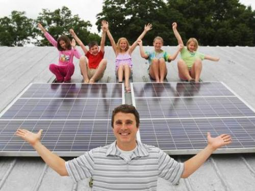 Teacher and students with school solar panels