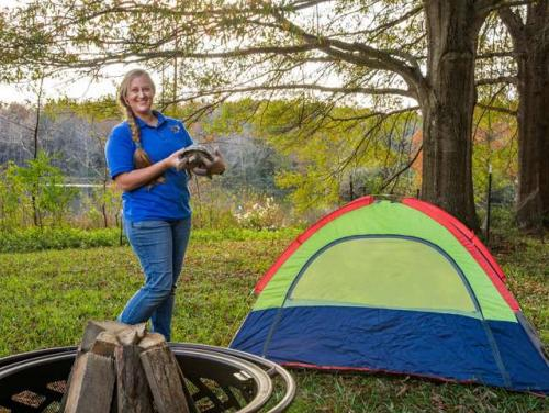 Person near tent and fire pit camping at the Zoo.
