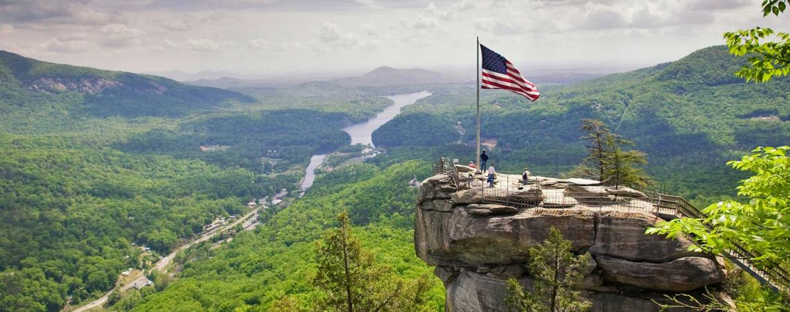 image of chimney rock state park with the american flag and mountains in background