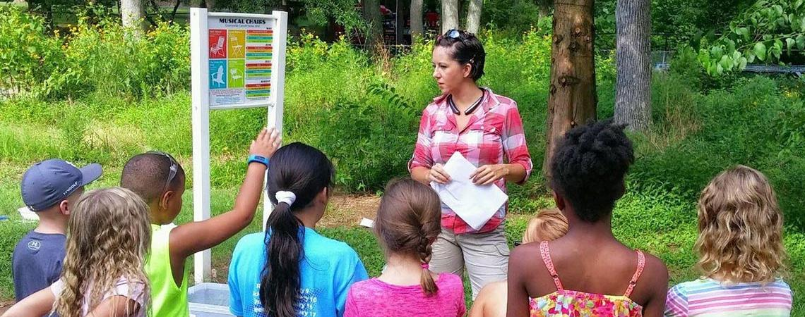 Instructor speaking to a group of children at an outdoor center
