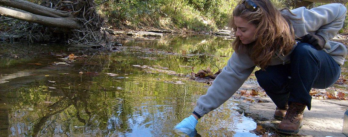 young woman takes water sample from stream