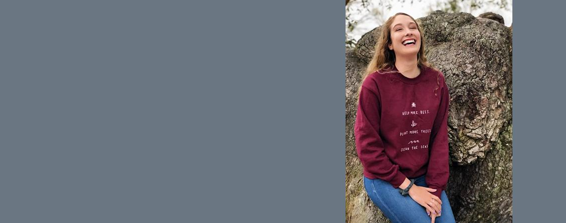 Cassie Skrutowski wearing a burgundy shirt and leaning against a huge rock