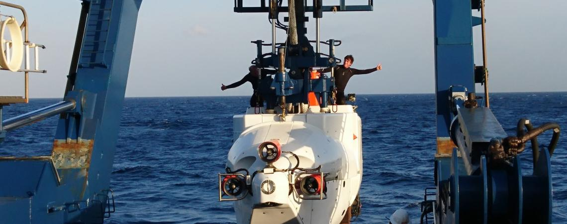 "photo of the lowering the ""Alvin"" a submersible with two people on top"
