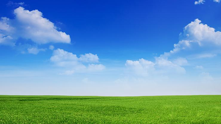 bright blue sky with a few clouds over a green field
