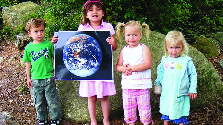 4 young children with a large photo of the earth