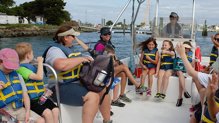 school group with coastal reserve educator on boat for a Coastal reserve field trip