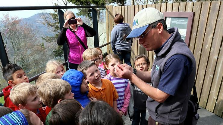 male instructor leads group of children on field trip
