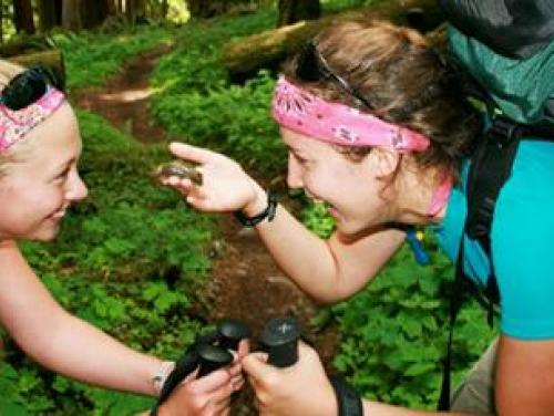 2 young women examine a frog on a hiking trail