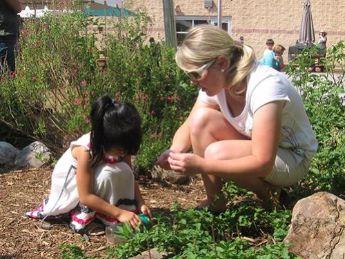 woman and young girl collect insects in a jar on play center grounds
