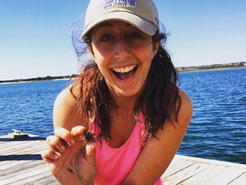 Certified environmental educator Nina Quaratella on an ocean dock holding a sea urchin