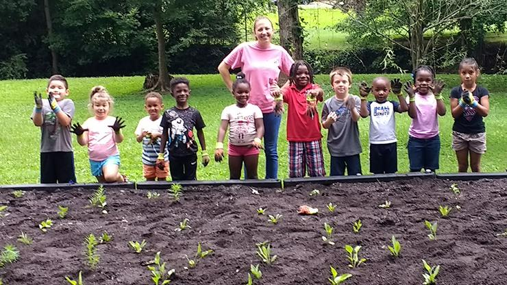 woman with a group of children behind a plot of seedlings