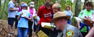 State Parks ranger shows a fern to a group of children
