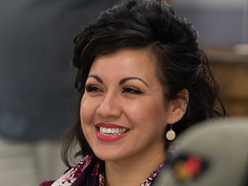 A woman in professional attire smiles while watching a presentation