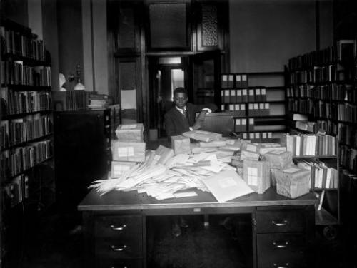 Young African American man observes mail and parcels in mail room