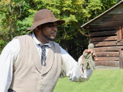 African American male actor in historic dress clutches rag doll.