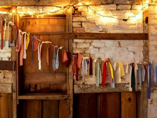 colorful cloths and lights hang from ceiling in historic cabin