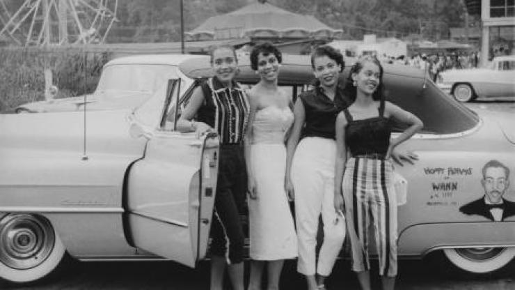Four young African American women pose in front of vehicle