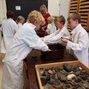 Kids work with lab technician to wash artifacts