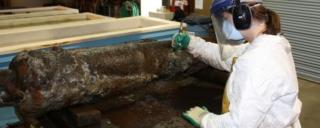 QAR conservator removes concretions from canon