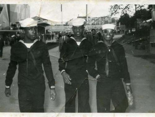 Photograph of Lawrence E. Allen (center) and two unidentified African American shipmates from an unidentified U.S. Navy ship [believed to be the USS Macon], pictured walking down the road wearing their U.S. Navy uniforms in Sweden. (CLDW 23.F3.13)