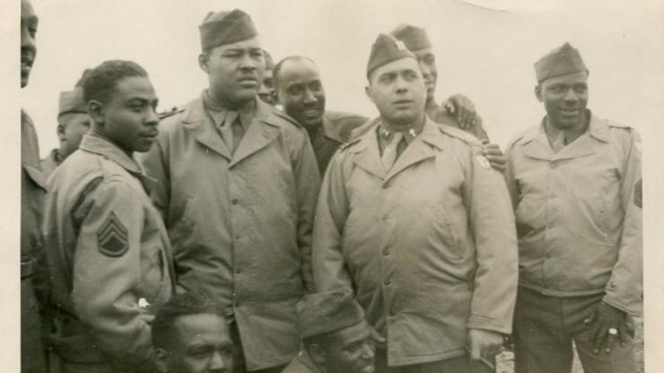Photograph of a group of African Army soldiers from the 364th Infantry Regiment (Colored), 92nd Infantry Division, posing with heavyweight boxing champion Joe Louis (second from left, foreground)