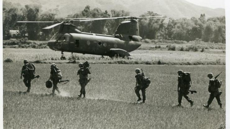 MMP 1.B10.F15.5: Photograph of unidentified armed troops on the ground in Vietnam with a U.S. Marine Corps Boeing Vertol CH-46 Sea Knight helicopter parked in the background, 1966.