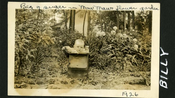 Photo of a baby in a box that is sitting in a garden. Written on photo: Bag of sugar in Maw Maw's flower gardern, 1926