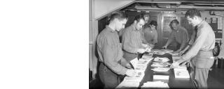 Photograph of U.S. Navy crew members of the Navy aircraft carrier USS Bunker Hill (CV-17), folding the ship's newsletter the Monument, taken while the ship was serving in the Pacific Theater in April 1945 during World War II.
