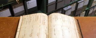 an open book with archival boxes in the background
