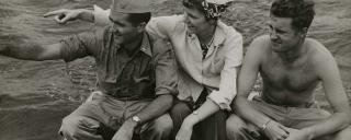 Annie Laurie Burton seated in a boat between two soldiers.
