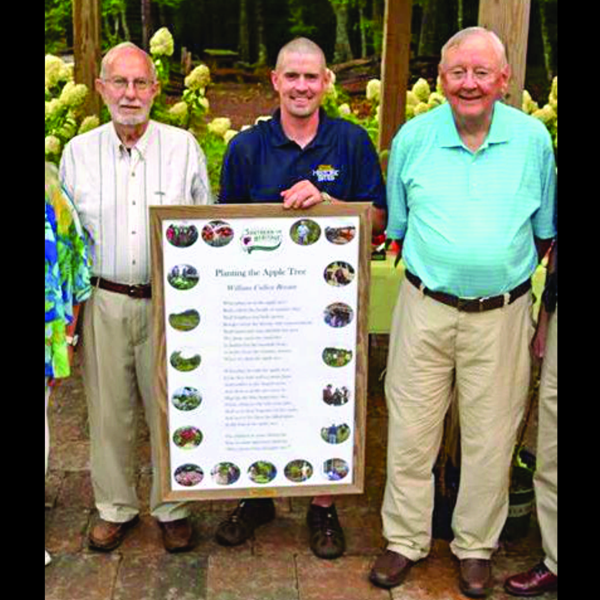 three men stand with a framed poem about an apple tree