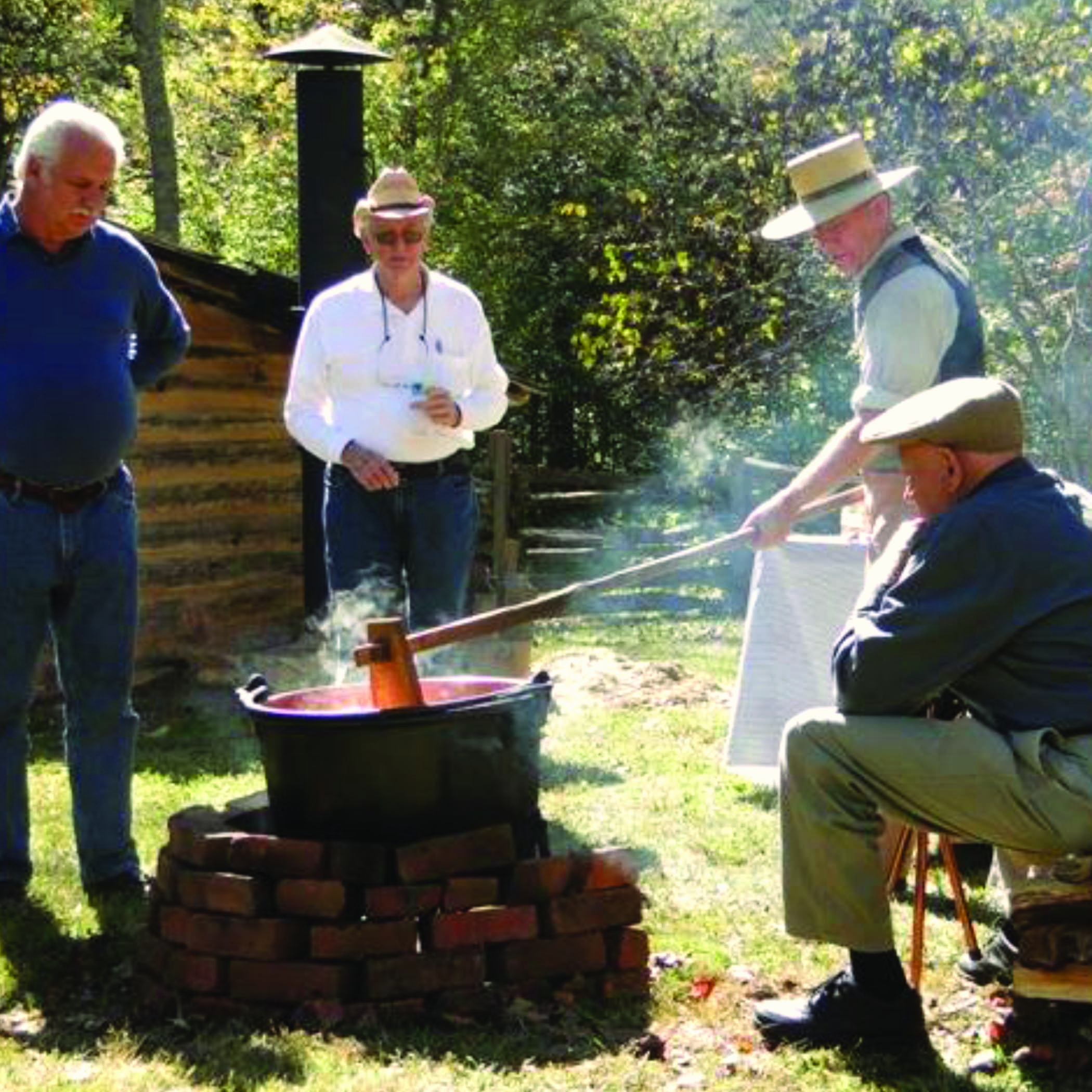 a man outside by a wood fire, stirring a pot of apple butter with a paddle. He is surrounded by onlookers