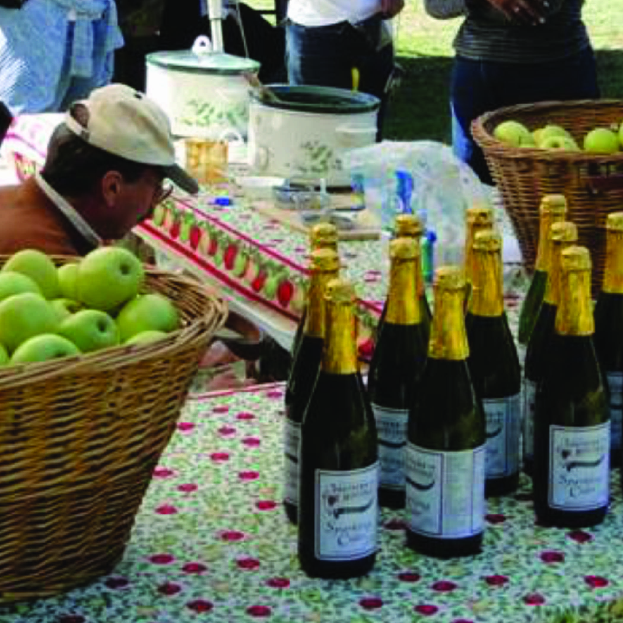a vendor's table with a basket of green apples and bottles of sparkling cider